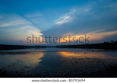 Cloudscape of sunset with blue sky and lake. - stock photo