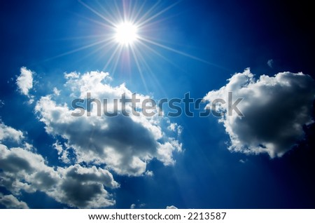 Cloudscape with bright sun and blue sky. High contrast. - stock photo