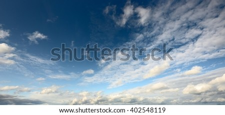 Cloudscape with ornamental cloud and dark blue sky - stock photo