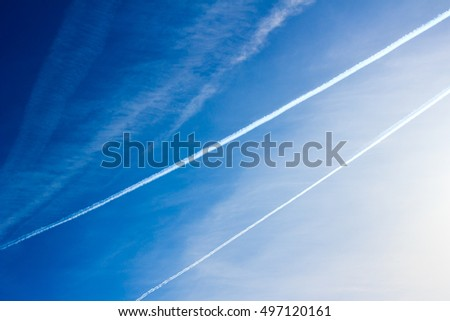 Cloudscape with trail of jet plane on blue sky. Natural background.