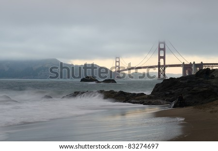 Cloudy and foggy Golden Gate Bridge with Baker Beach in San Francisco - stock photo