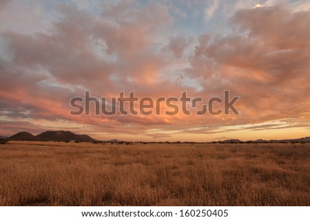 Cloudy colorful Autumn sunset over dry grassland and hills in semi-desert/Uplifting Orange and Blue Clouds in Autumn Dusk over dry Grassland Prairie/Colorful Fall clouds in rural desert Southwest USA - stock photo