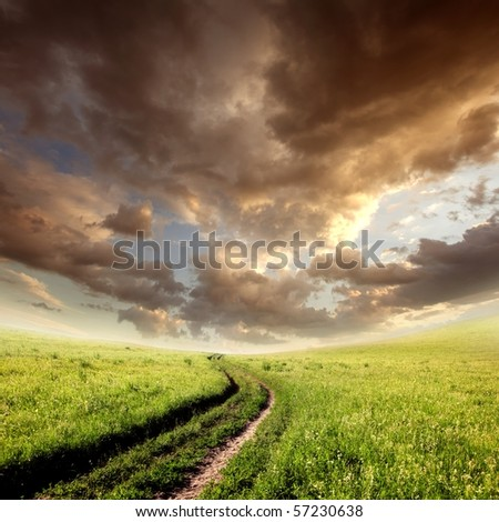 cloudy field with green grass, road and clouds - stock photo