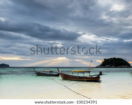 Cloudy morning on a tropical island. Visible sun rays throughout clouds. - stock photo