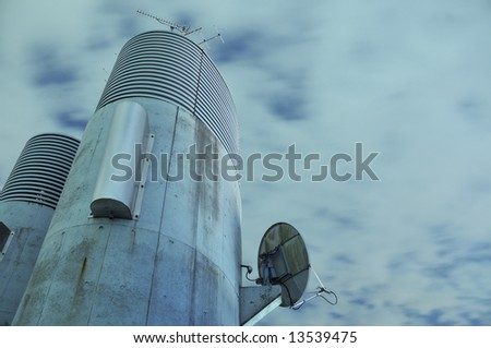 cloudy night sky over concrete communication tower with sat receiver on the wall and antenna on the top - stock photo