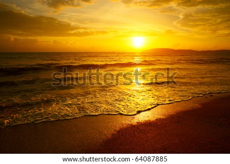 Cloudy orange sunset over sea - stock photo