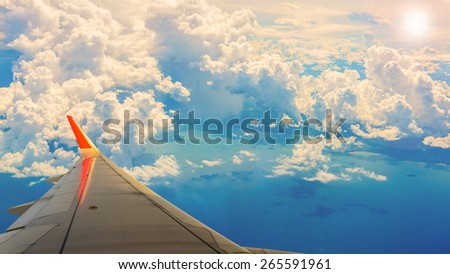 cloudy sky and airplane wing as seen through window of an aircraft. - stock photo