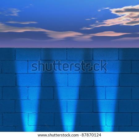 cloudy sky and blue brick wall with headlight illumination - stock photo