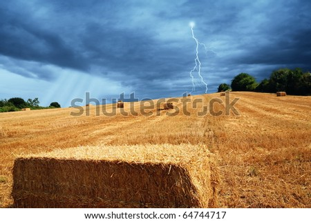 cloudy sky and field  on the hill after threshing - stock photo