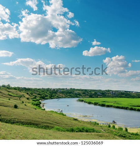 cloudy sky and river in green landscape - stock photo