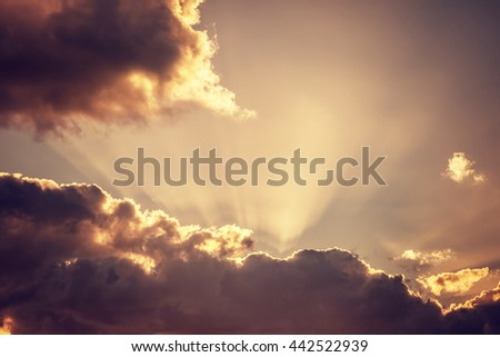 Cloudy sky background, bright sunbeams through dark clouds, message from God, overcast autumn weather - stock photo