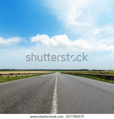 cloudy sky over asphalt road - stock photo