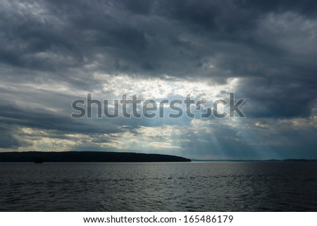 Cloudy sky over the lake. Rays of light through the clouds. - stock photo
