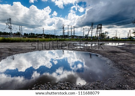 Cloudy Sky Reflected in Huge Road Puddle near Moscow, Russia - stock photo