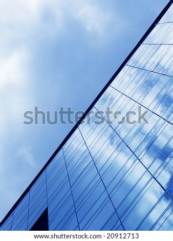Cloudy sky reflected in the glass wall of a high-rise building
