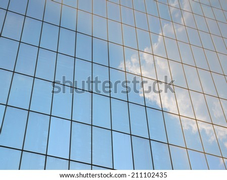 Cloudy sky reflected in the windows of a skyscraper - stock photo