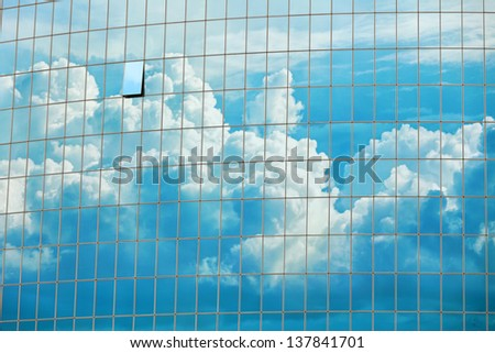 Cloudy sky reflected in the windows of a skyscraper - urban background - stock photo