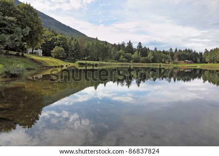 Cloudy sky reflected in water, a small lake in the mountains of northern Italy.