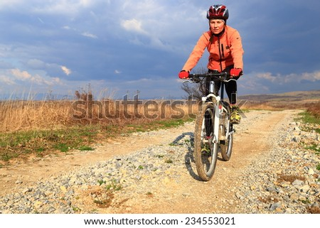 Cloudy sky upon young woman cycling on a dirt road in sunny day - stock photo