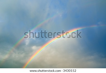 Cloudy sky with double rainbow (can be used how background or wallpaper) - stock photo