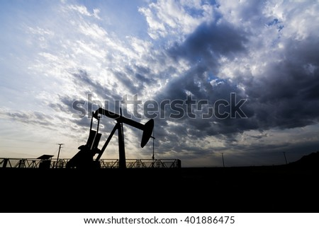Cloudy sunset and silhouette of crude oil pump in oil field.