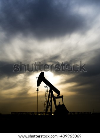 Cloudy sunset and silhouette of crude oil pump in oilfield  - stock photo