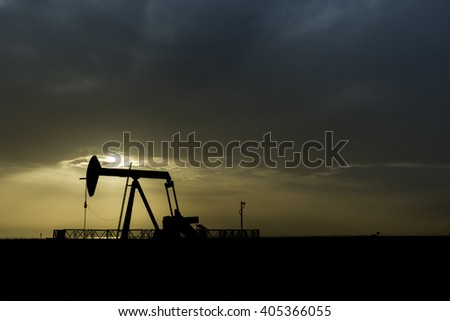 Cloudy Sunset and silhouette of crude oil pump unit in oilfield
