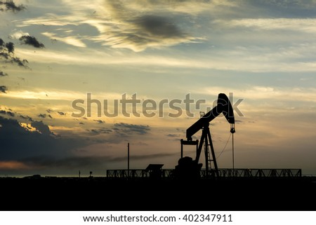 Cloudy sunset and silhouette of crude oil pumping unit in the oil field.