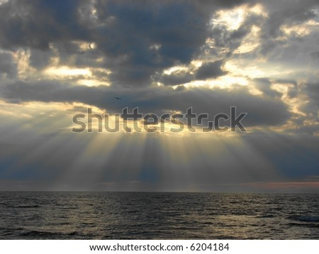 Cloudy sunset over Baltic Sea. Looks like rays from heaven - stock photo