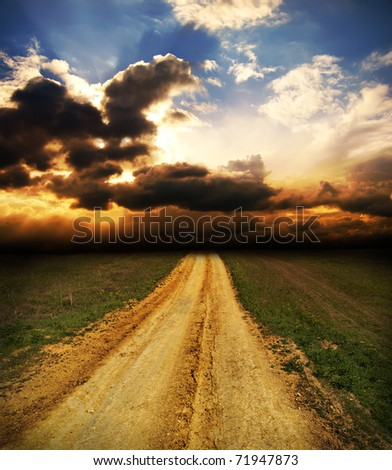 cloudy sunset over dirty road - stock photo