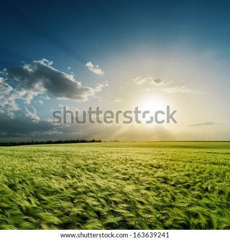 cloudy sunset over green field