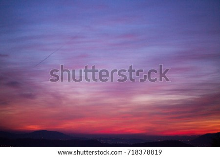 Cloudy sunset sky. Orange, pink and blue. Natural lens blur.