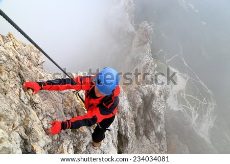 "Cloudy weather and young woman climbs steep ridge on via ferrata ""Punta Ana"", Tofana massif, Dolomite Alps, Italy - stock photo"