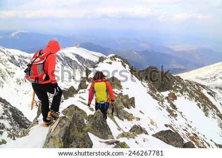 Cloudy weather on the mountains and team of climbers during descent in winter - stock photo