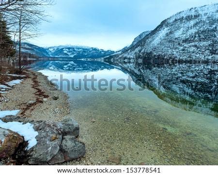 Cloudy winter Alpine  lake Grundlsee view (Austria) with fantastic pattern-reflection on the water surface. - stock photo