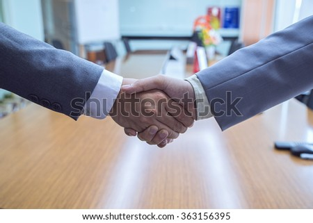 Clouse-up of businessman and businesswoman shaking hands in Meeting room - stock photo