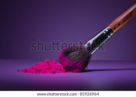 Clouse-up of makeup brush and face powder on purple background - stock photo