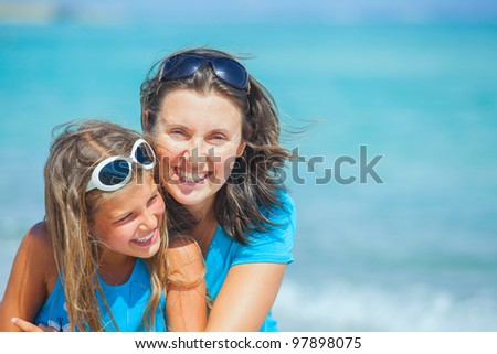Clouseup portrait of mother and her daughter having fun on tropical beach