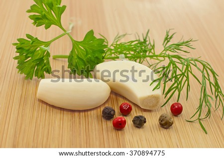 cloves of garlic, dill, parsley and pepper mixture on a wooden background