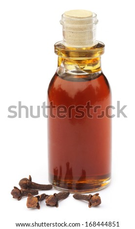 Cloves with essential oil over white background - stock photo