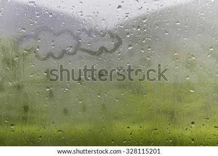 Clowds drawn on the foggy glass window on a raining day - stock photo