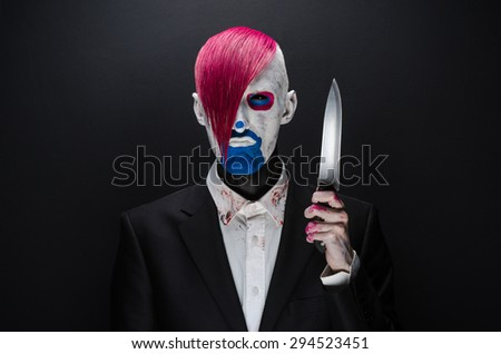 Clown and Halloween theme: Scary clown with pink hair in a black suit with a knife in his hand on a dark background in the studio - stock photo