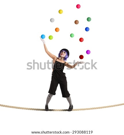 Clown as juggler is balancing on rope - stock photo