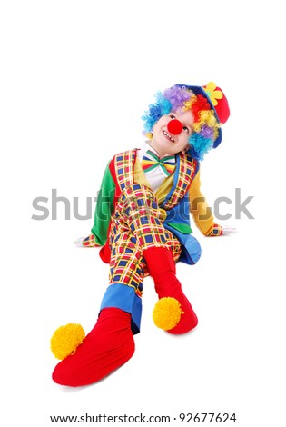 Clown child sitting on the floor and looking overhead over the white background - stock photo