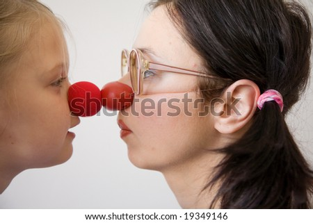 Clown-doctor : red nose contact of clown with kid. Profiles of woman and girl.