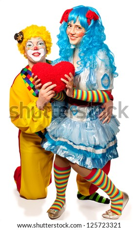 Clown giving his heart actress.Valentine day. Isolated on white