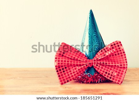 clown hat and big bow tie over wooden table. filtered image.  - stock photo