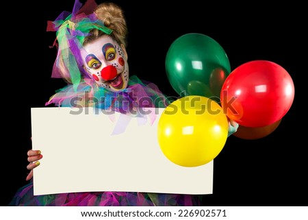 Clown holding a poster and three colorful balloons in hands - stock photo