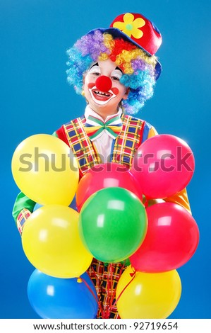 Clown holding balloons over the blue background - stock photo