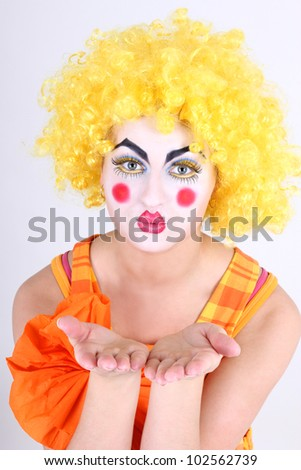 Clown in colorful costume with make-up showing hands
